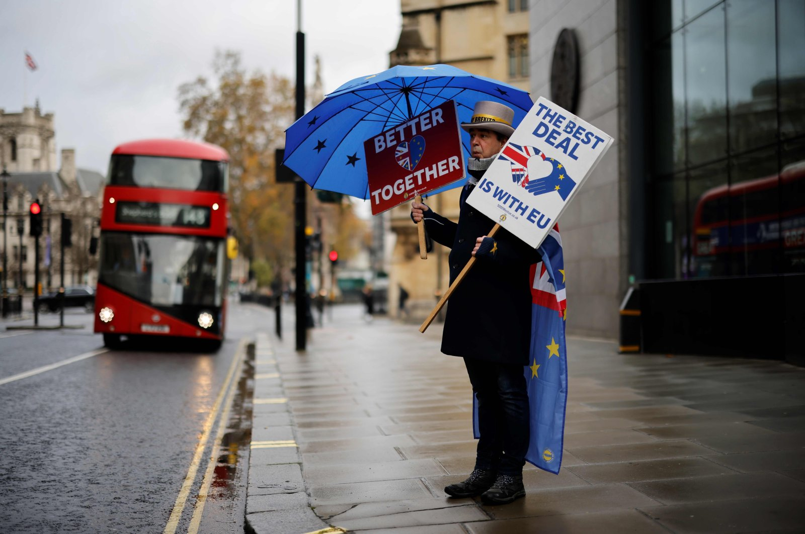 An anti-Brexiteer activist holds placards and an EU-themed umbrella as he stands outside a conference center, London, Dec. 4, 2020. (AFP Photo)
