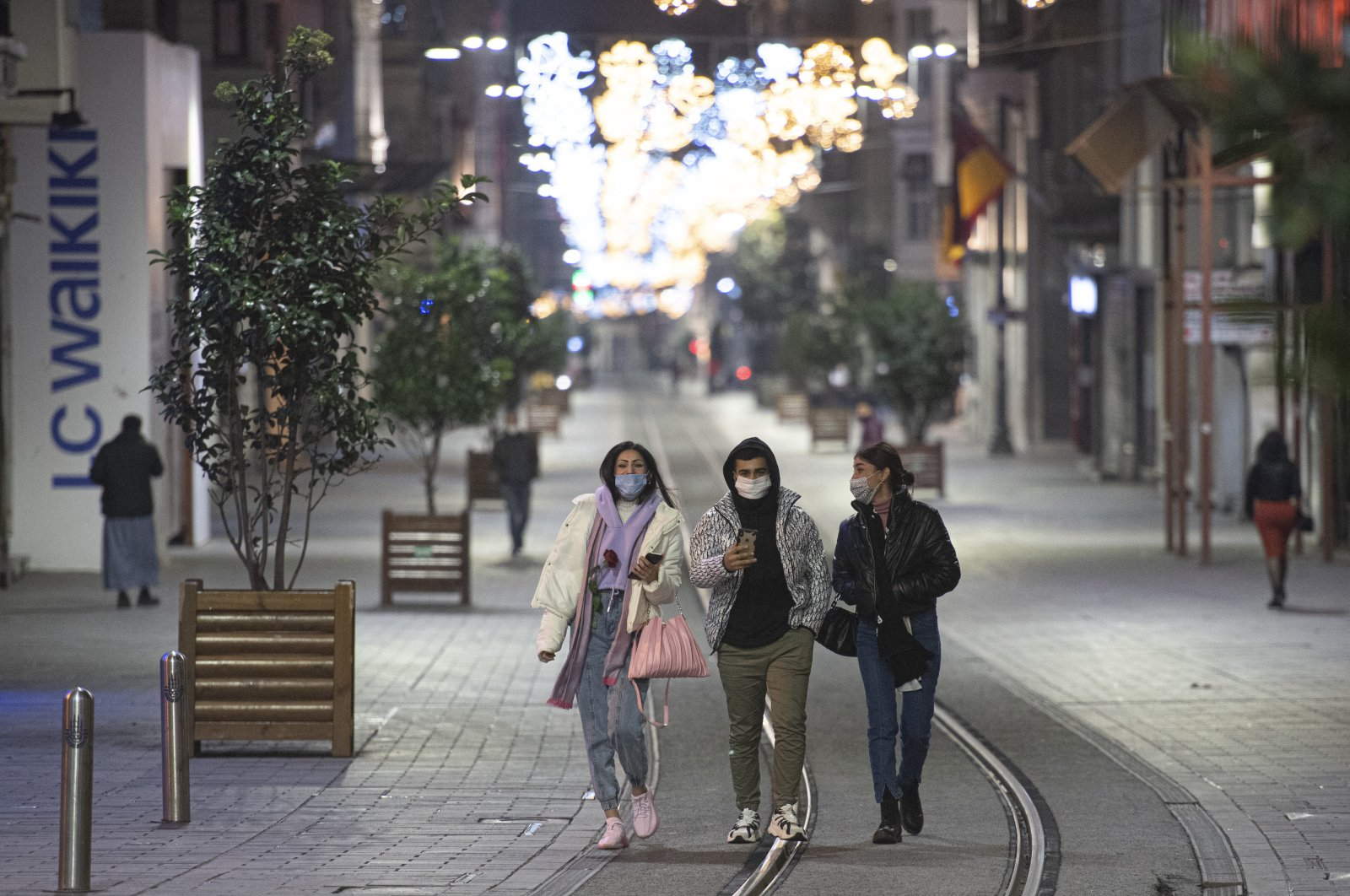 People walk on Istiklal street, the main shopping street in Istanbul, during a curfew on Dec. 1, 2020. (AP Photo)