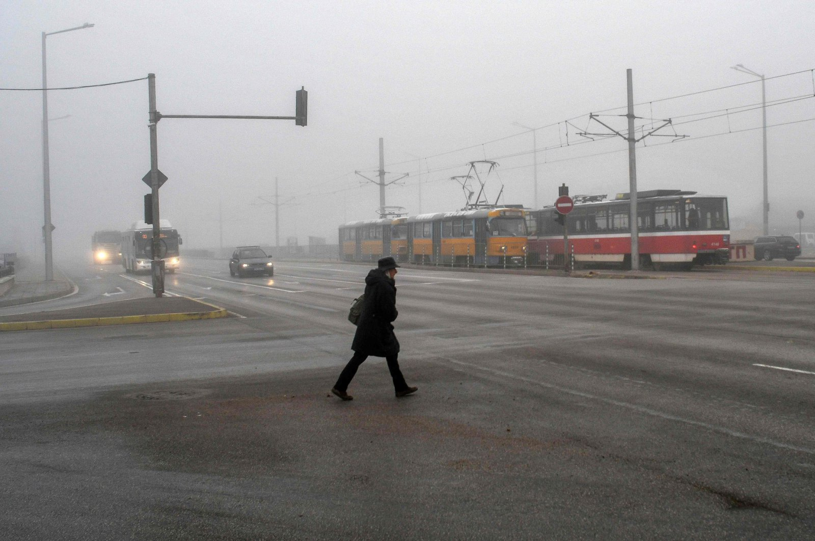 A woman crosses a street, early in the morning, amid the smog covering Sofia on Nov. 27, 2020. (AFP Photo)