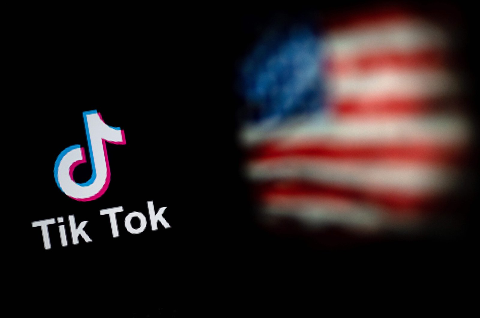 The logo of the social network application TikTok (L) and a U.S. flag seen on the screens of two laptops in Beijing, Sept. 14, 2020. (AFP Photo)
