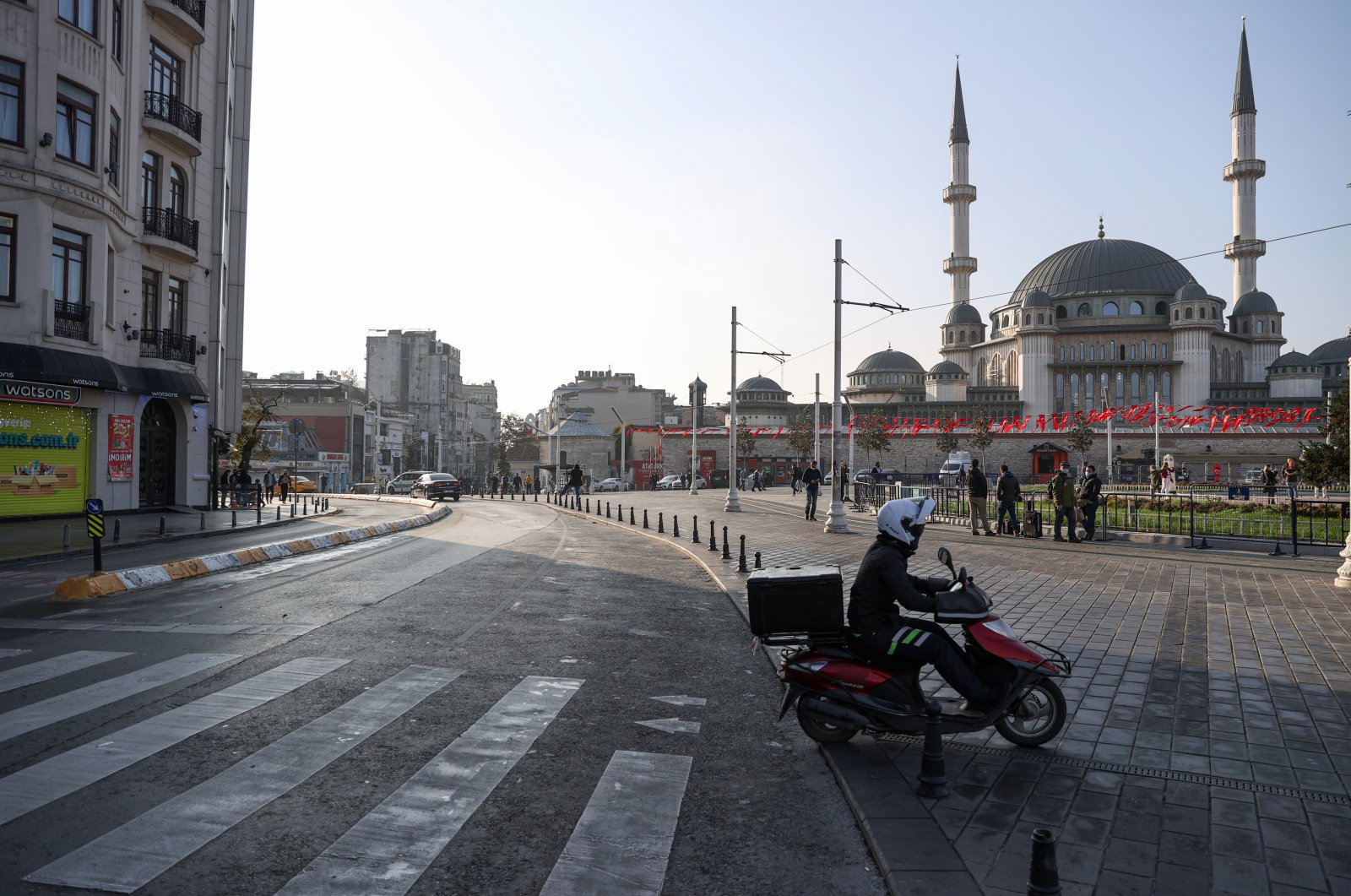 A motorcycle delivery personnel crosses a nearly empty Taksim Square in Istanbul during the second day of COVID-19 curfew in effect throughout Turkey, on Dec. 05, 2020. (AA Photo)