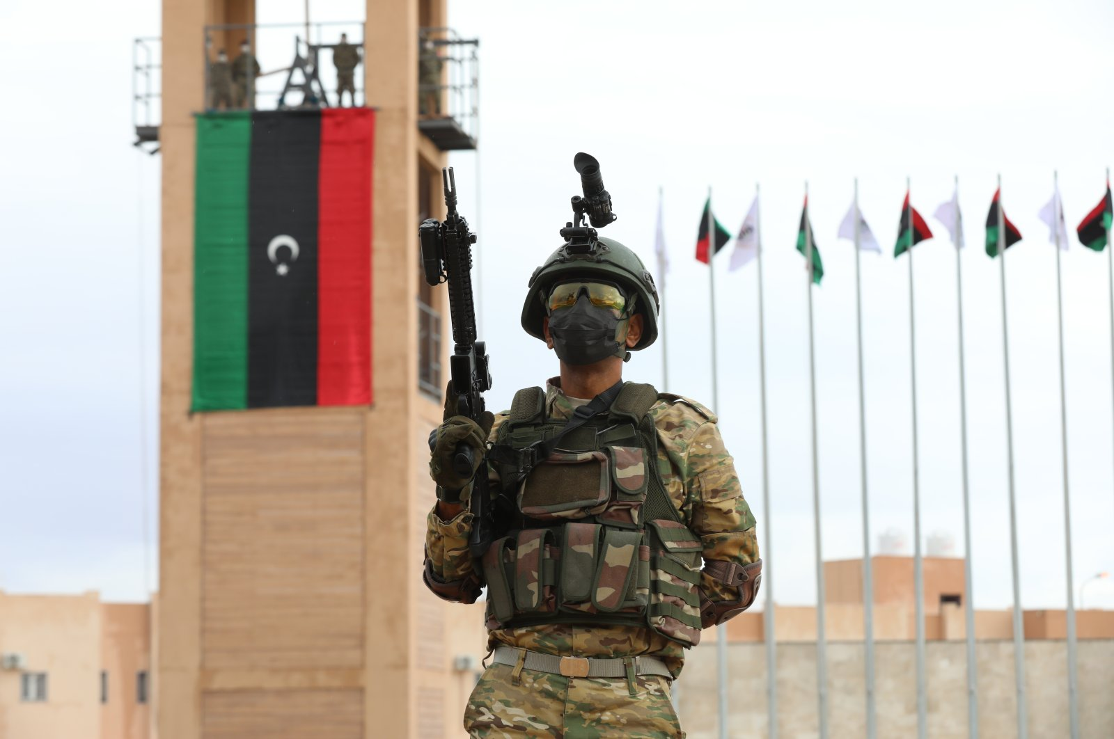 A Libyan soldier poses in front of the Libyan flag during a graduation ceremony concerning a military training program between Ankara and Tripoli, where the joint land training center Omar Mukhtar is located, on Nov. 21, 2020. (AA Photo)