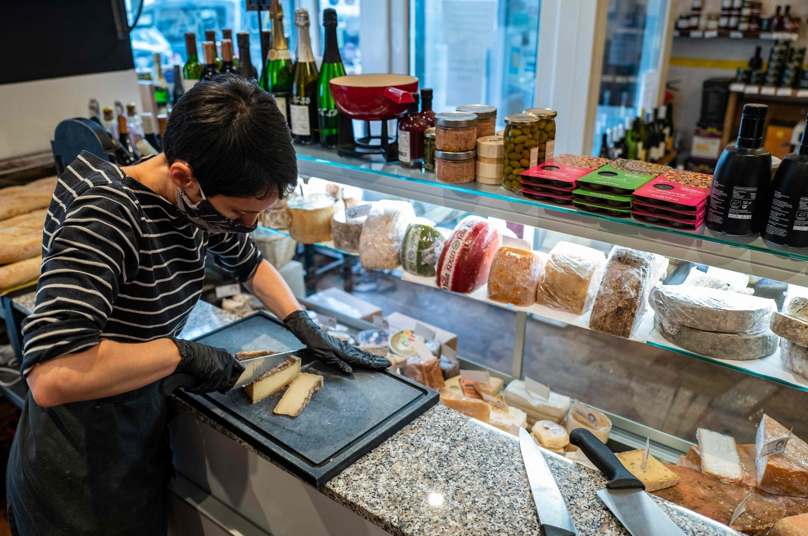 An employee at the restaurant La Cantine d'Augusta prepares the cheese in this newly refurbished restaurant in Berlin's Schoeneberg district, Germany, Nov. 11, 2020. (AFP Photo)