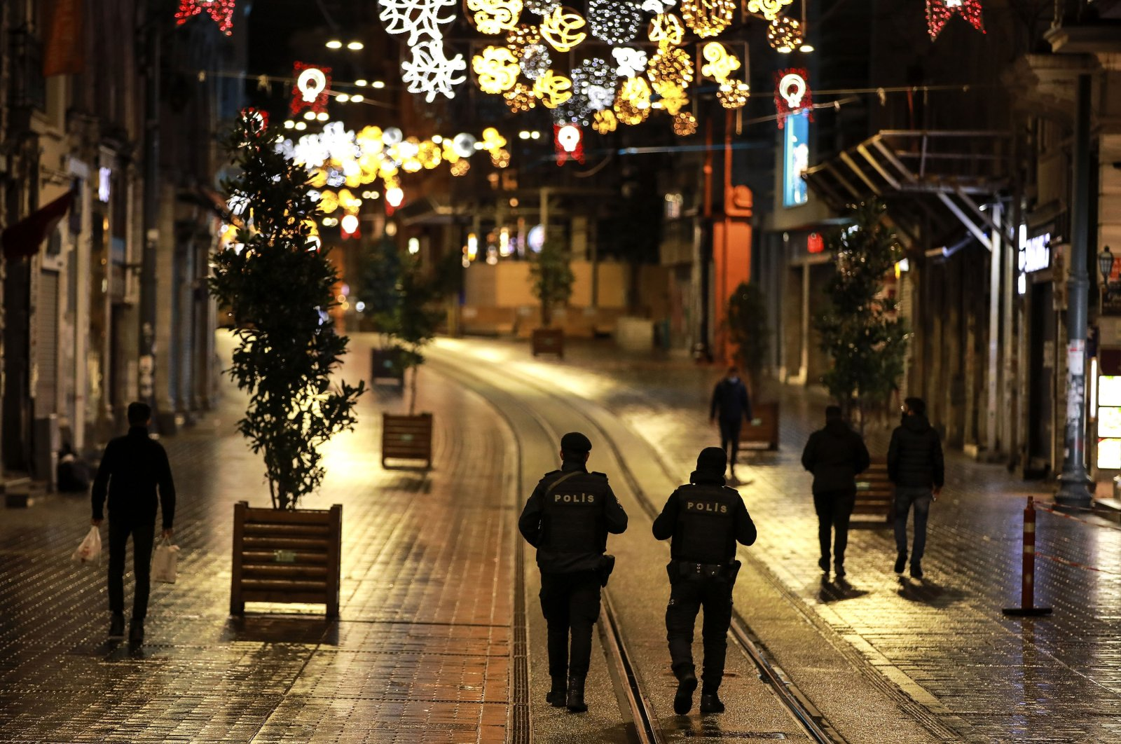 Police officers patrol Istiklal street, the main shopping street in Istanbul, minutes into the lockdown, part of the new measures to try to curb the spread of the coronavirus on Nov. 21, 2020. (AP Photo)