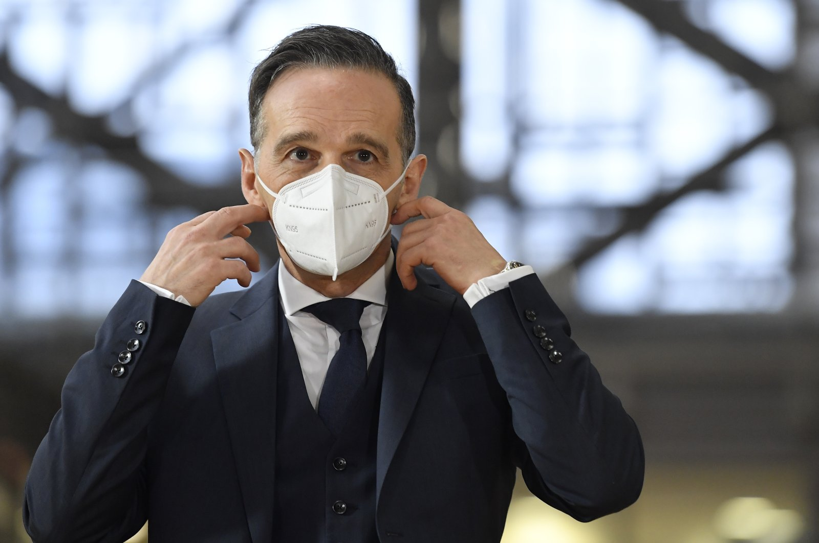 German Foreign Minister Heiko Maas takes off his protective mask as he arrives for a meeting of EU Foreign Ministers at the European Council building in Brussels, Belgium, Dec. 7, 2020. (AP Photo)