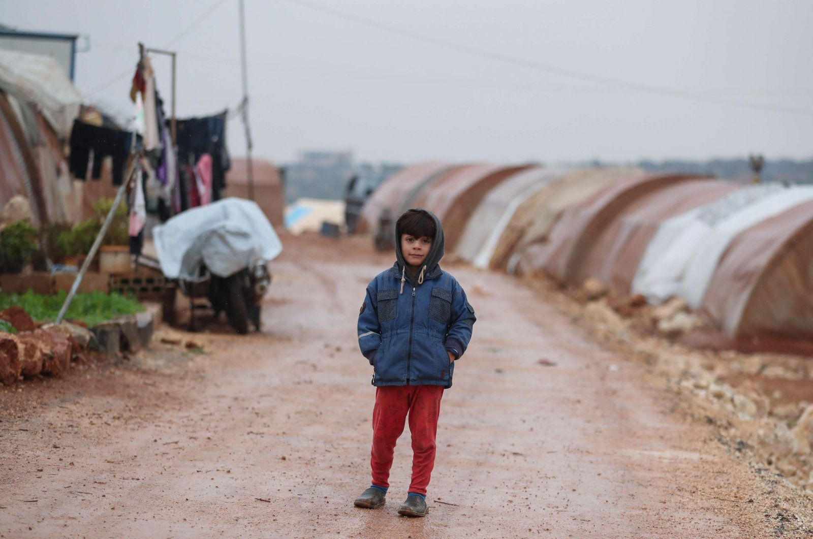 A boy poses for a picture at the Batinta camp for the internally displaced after heavy rainfall in northwestern Idlib province, northern Syria, Nov. 26, 2020. (AFP Photo)