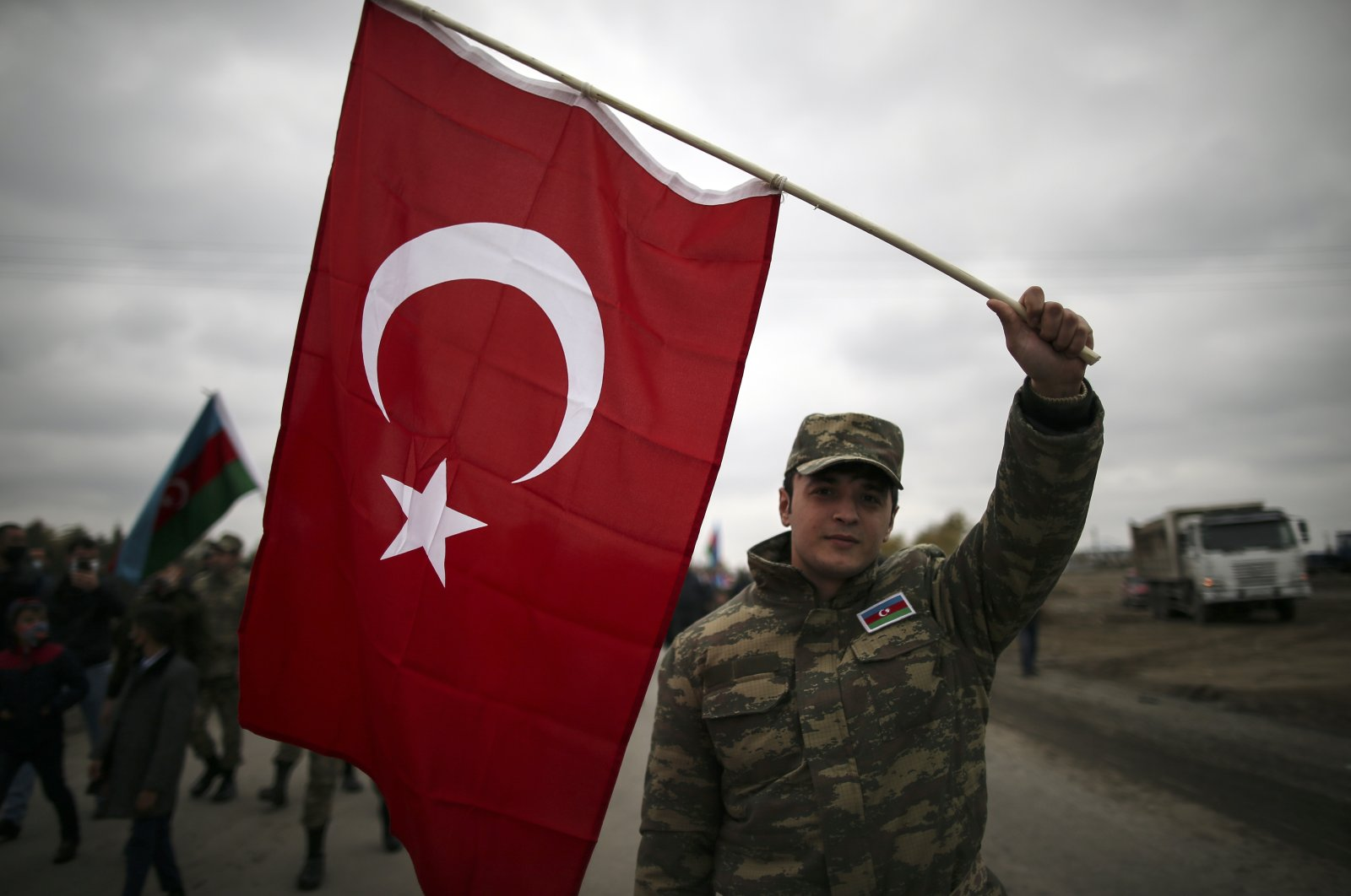 An Azerbaijani soldier holds a Turkish national flag as he celebrates the transfer of the Lachin region to Azerbaijan's control, in Aghjabadi, Azerbaijan, Dec. 1, 2020. (AP Photo)