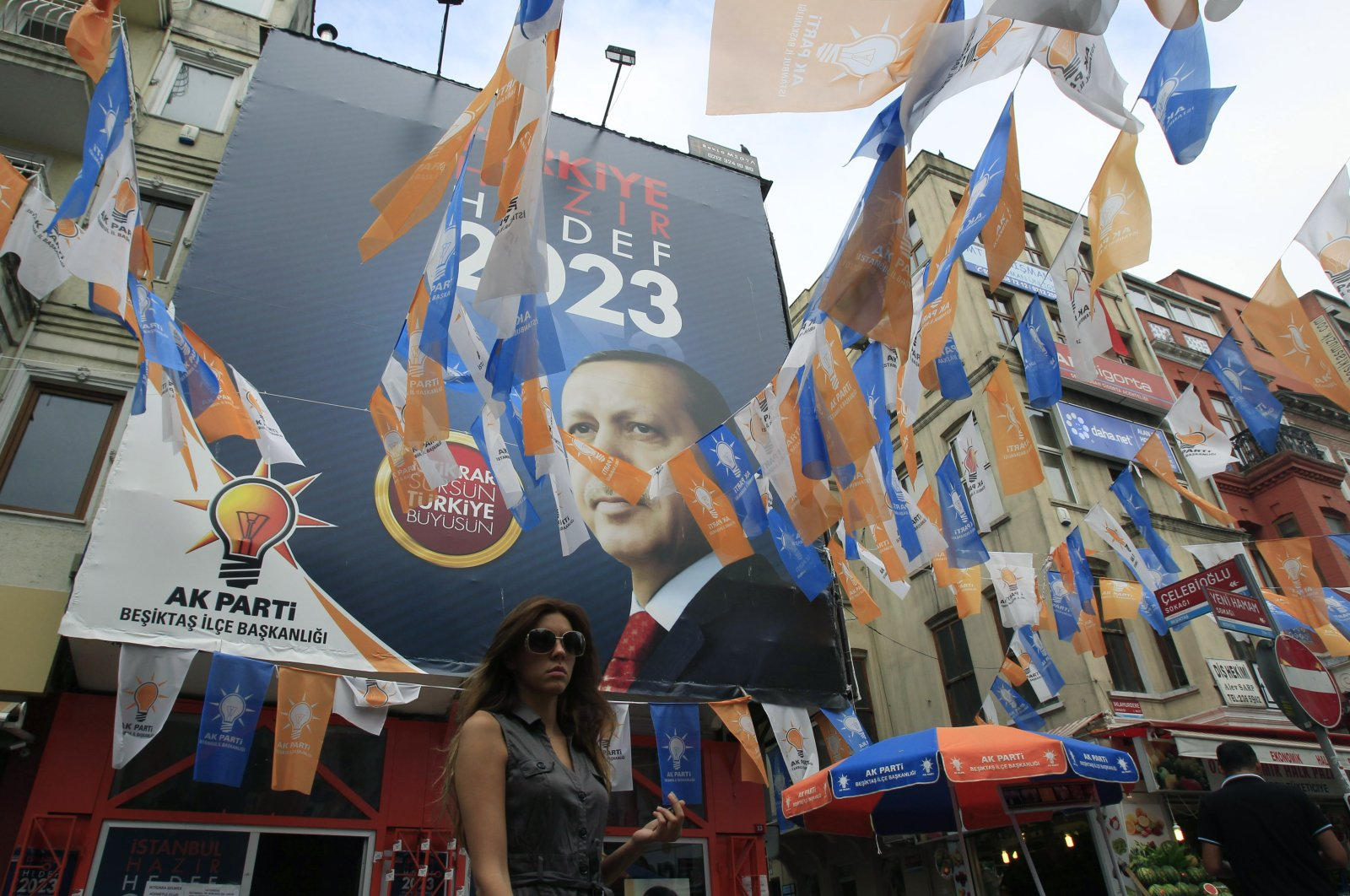 A pedestrian passes an election center for the AK Party displaying a photo of Recep Tayyip Erdoğan, in Istanbul, Saturday, June 11, 2011. (AP Photo)