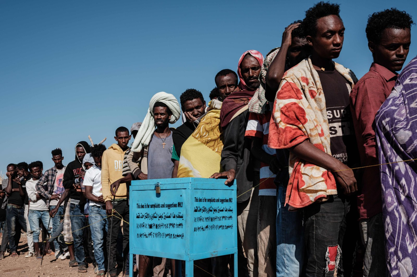 Newly arrived Ethiopian refugees who fled the Tigray conflict queue next to a complaint and suggestion box in Gedaref, eastern Sudan, Dec. 6, 2020. (AFP Photo)