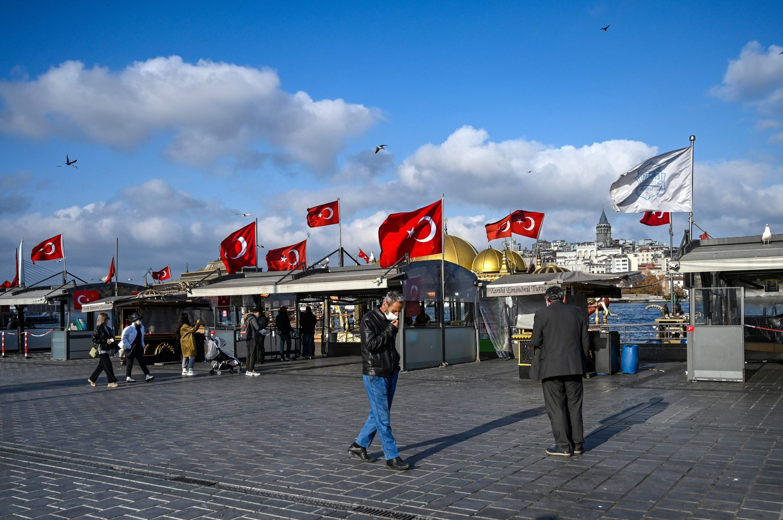 People walk in a deserted Eminönü Square in Istanbul near closed food stalls during a weekend curfew aimed at curbing the spread of the COVID-19 pandemic, Turkey, Dec. 6, 2020. (AFP Photo)