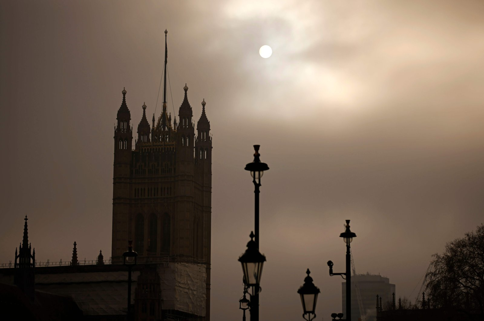The sun is seen through the fog behind the Victoria Tower, part of the Palace of Westminster, home of the Houses of Parliament in central London on December 7, 2020. (AFP Photo)