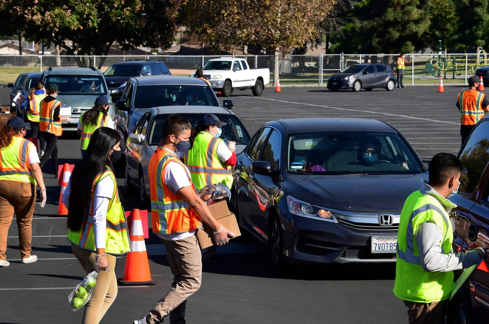 """Food is loaded as drivers in their vehicles wait in line on arrival at a """"Let's Feed LA County"""" food distribution hosted by the Los Angeles Food Bank in Hacienda Heights, California, on Dec. 4, 2020. (Photo by Frederic J. BROWN / AFP)"""