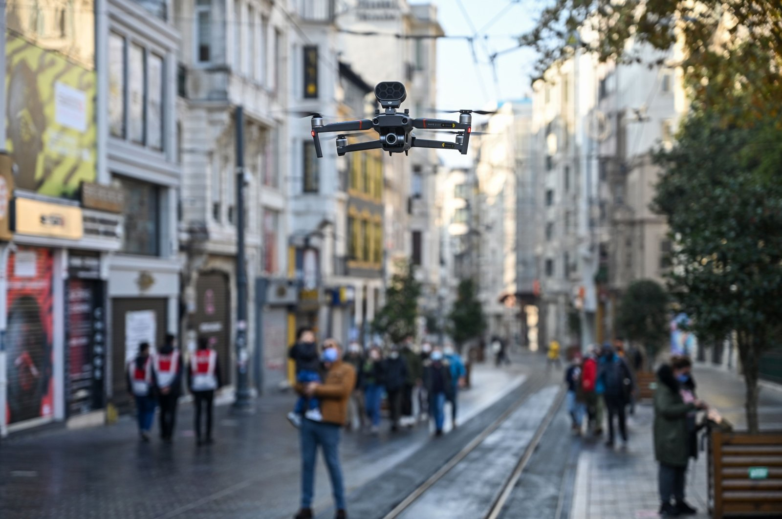 A Turkish police drone announces social distancing rules in English via a speaker as people walk on Istiklal avenue during a weekend curfew aimed at curbing the spread of the COVID-19 pandemic, Istanbul, Dec. 5, 2020. (AFP Photo)