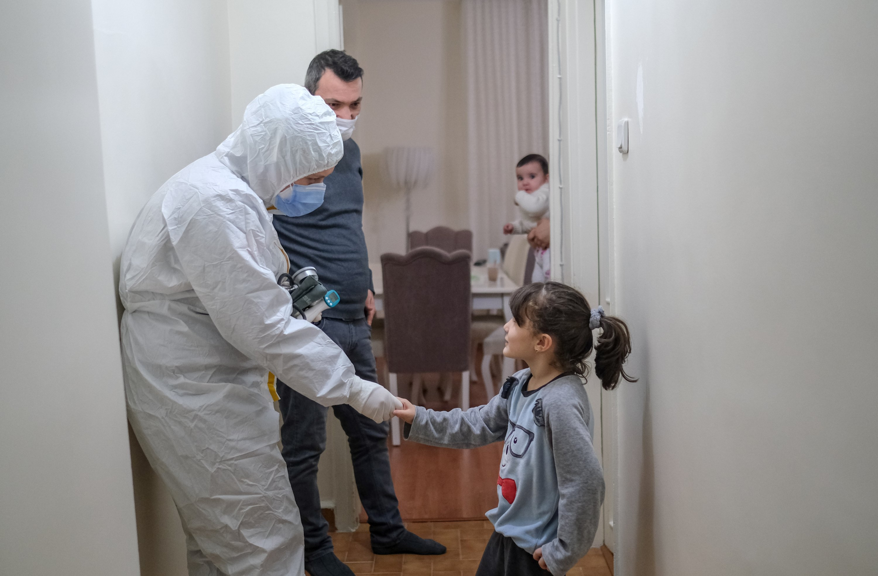 The crew greets a family during one of the house visits in their shift, in Istanbul, Turkey, Dec. 4, 2020. (PHOTO BY UĞUR YILDIRIM)