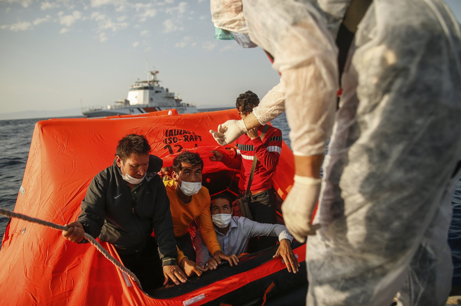 Turkish Coast Guard Command officers on their vessel, wearing protective gear to help prevent the spread of the coronavirus, talk to migrants on a life raft during a rescue operation in the Aegean Sea, between Turkey and Greece, Sept. 12, 2020. (AP File Photo)