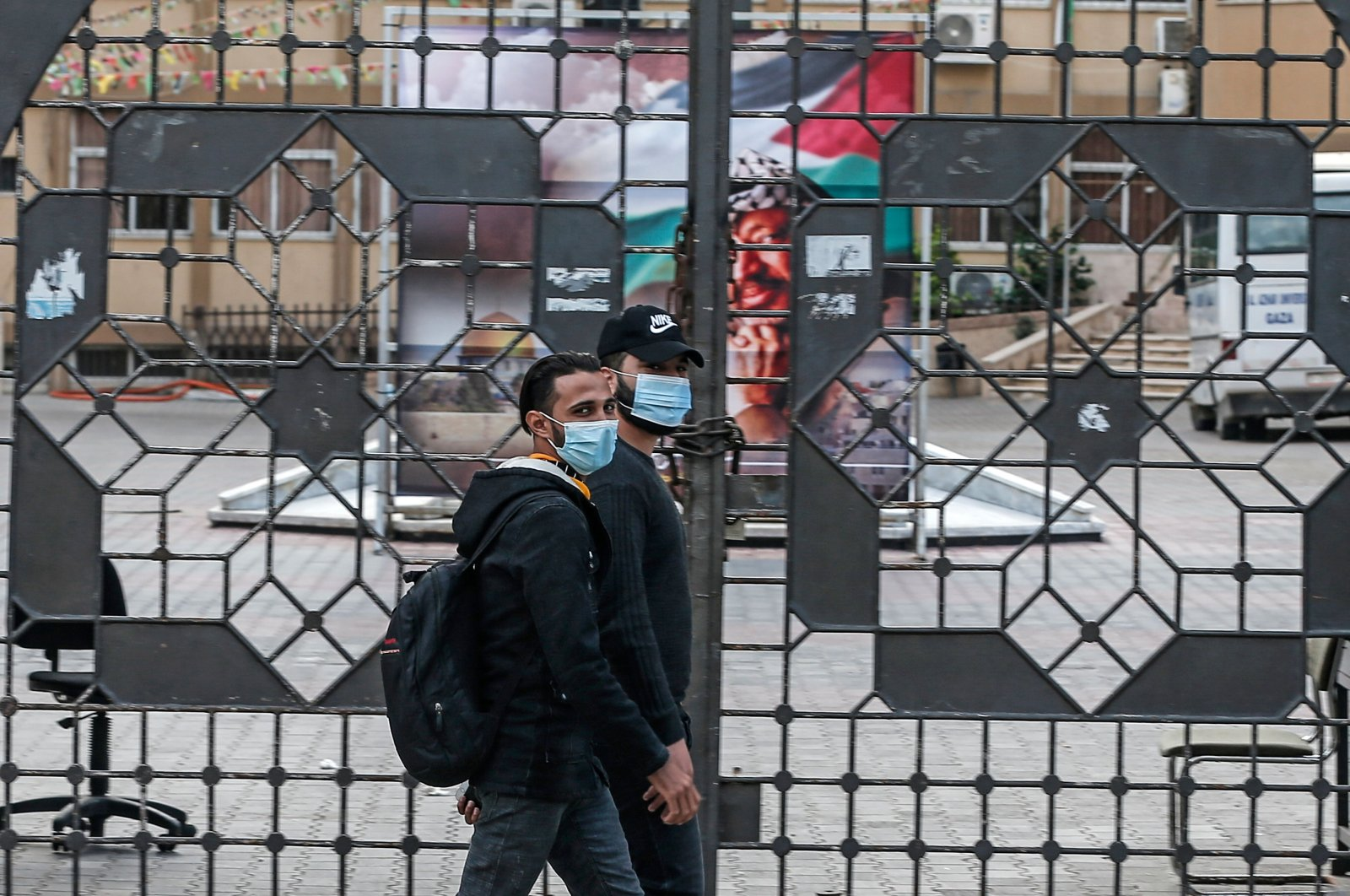 Palestinian men, wearing protective masks, walk past the closed gate of al-Azhar University in Gaza City amid new measures to counter the spread of the COVID-19 pandemic, Nov. 5, 2020. (AFP Photo)