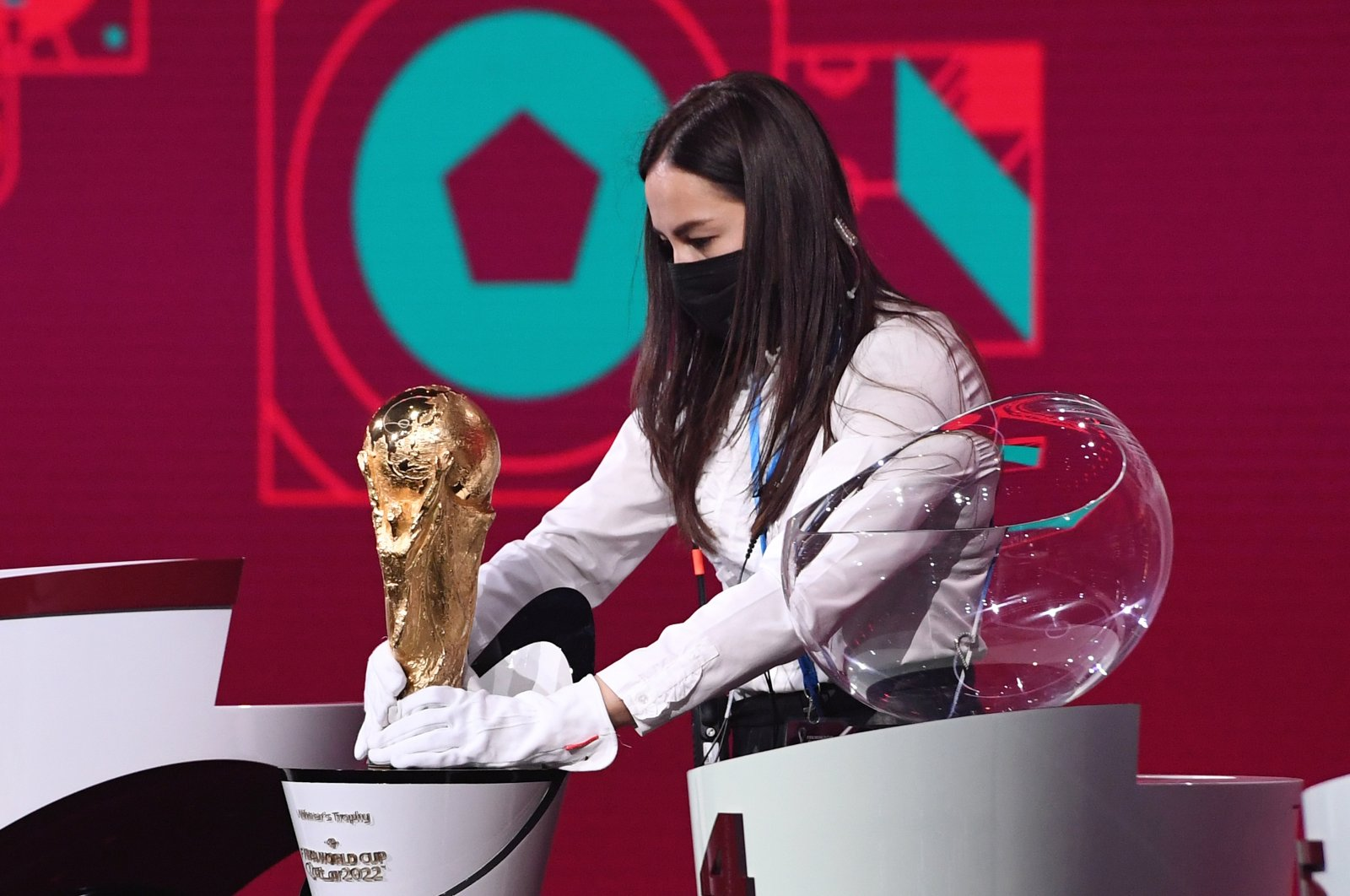 An event official carefully positions the World Cup trophy during the draw in Zurich, Switzerland, Dec. 7, 2020. (REUTERS PHOTO)