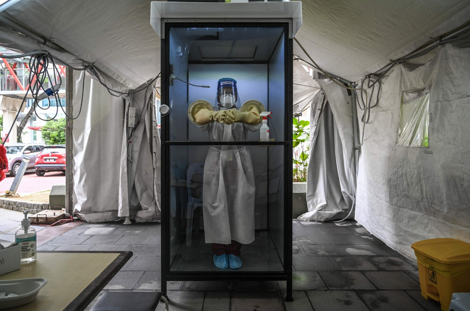 """A health worker stands inside a noncontact chamber called the """"CoV SHIELD"""" before taking swab samples to test for the coronavirus at Sunway Medical Center in Subang Jaya, on the outskirts of Kuala Lumpur, Oct. 22, 2020. (AFP Photo)"""