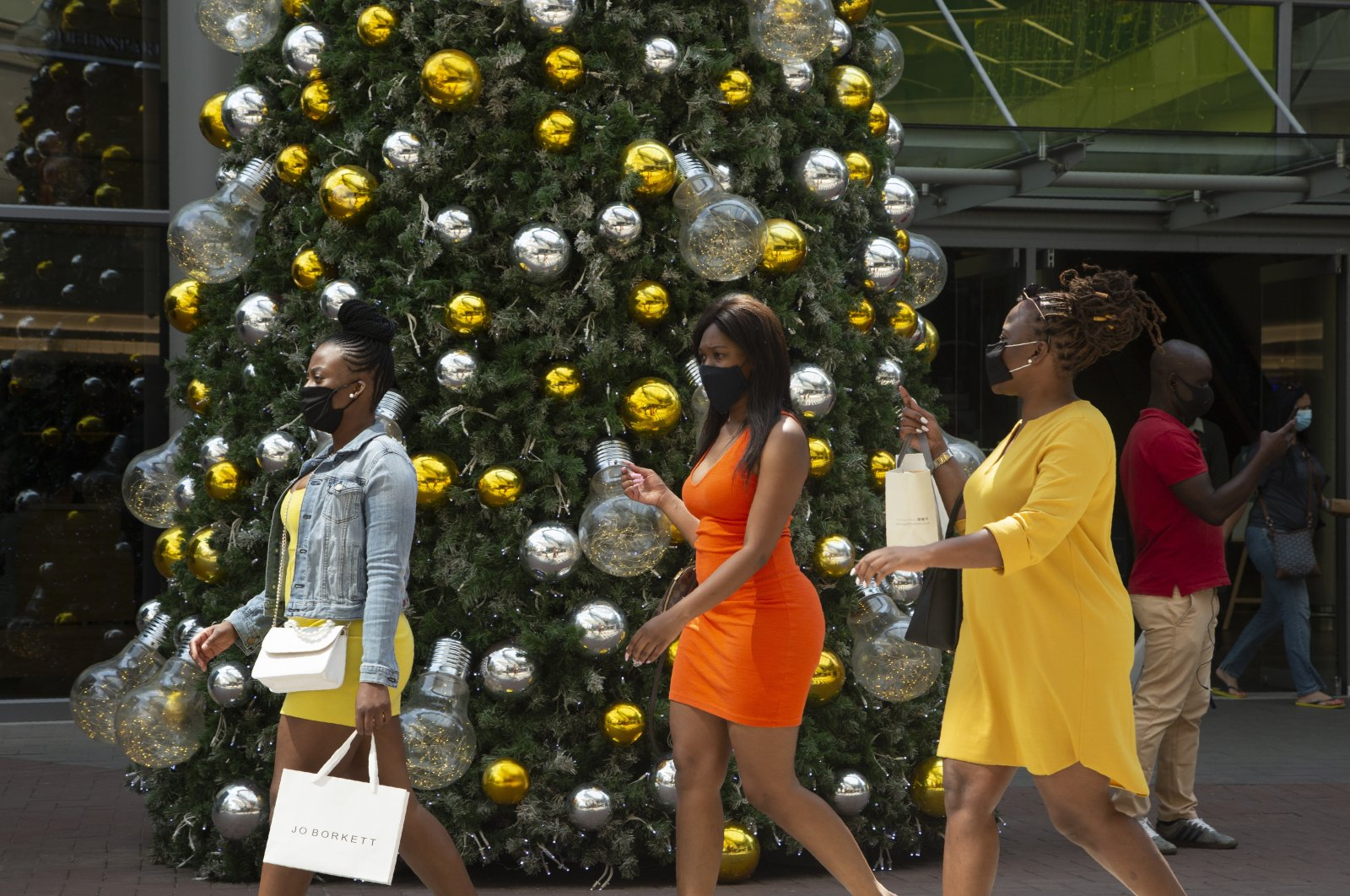 Women wearing face masks as protection against COVID-19 pass a Christmas tree at a shopping mall in Johannesburg, South Africa, Dec. 7, 2020. (AP Photo)