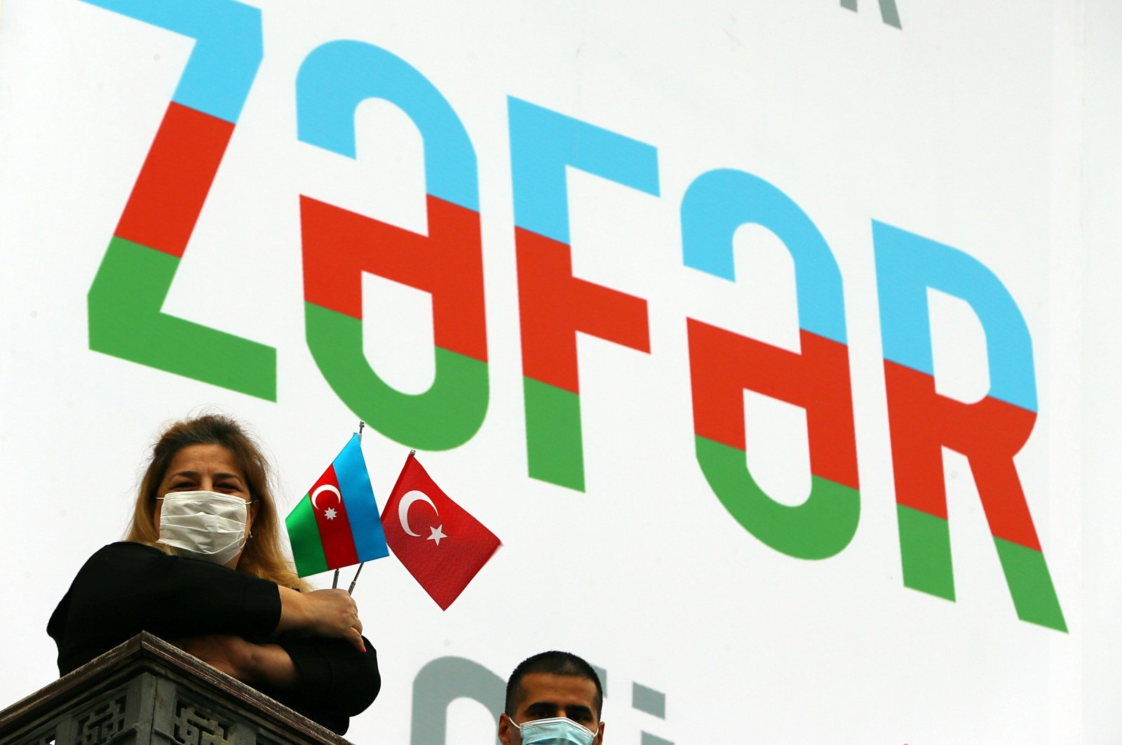 "Citizens holding Azerbaijani and Turkish flags stand in front of a poster that reads ""Zafar"" (""Victory"") amid preparations for the victory parade in the capital Baku, Azerbaijan, Dec. 8, 2020. (AA Photo)"