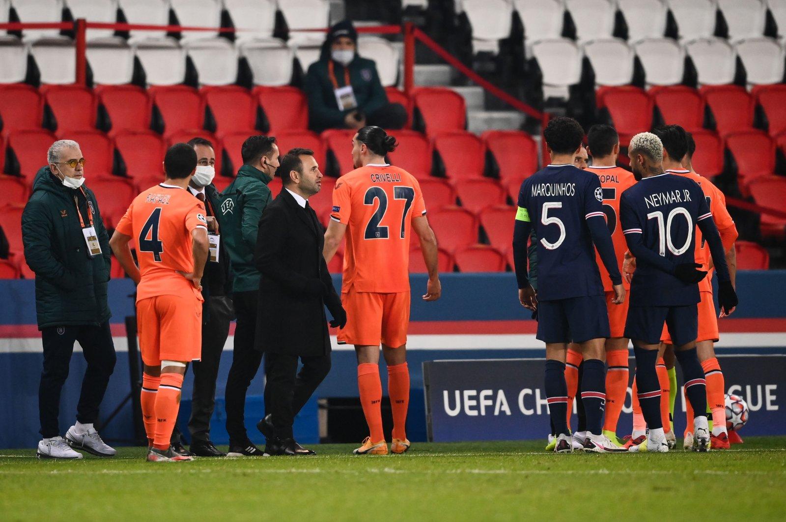 Başakşehir's coach Okan Buruk (3rd left, front) stands on the sideline as players argue during the UEFA Champions League match against PSG at the Parc des Princes stadium in Paris, France, Dec. 8, 2020. (AFP Photo)