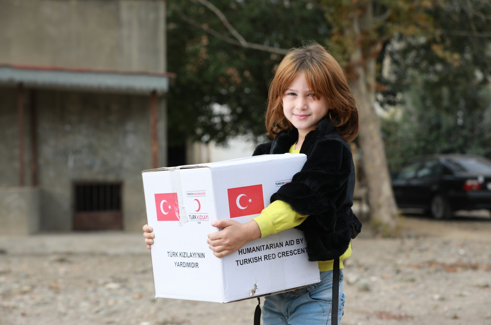 A little girl holds an aid package provided by the Turkish Red Crescent (Kızılay), Dec. 9, 2020. (DHA Photo)
