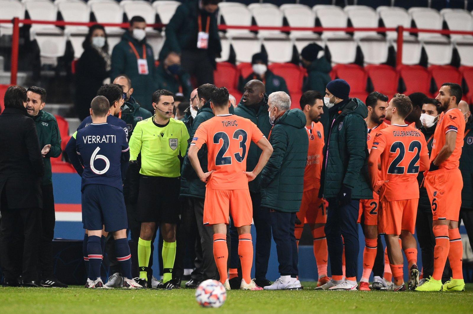 Romanian referee Ovidiu Hategan (in yellow) talks to Başakşehir staff members past and players during the UEFA Champions League match against Paris Saint-Germain at the Parc des Princes stadium in Paris, France, Dec. 8, 2020. (AFP Photo)