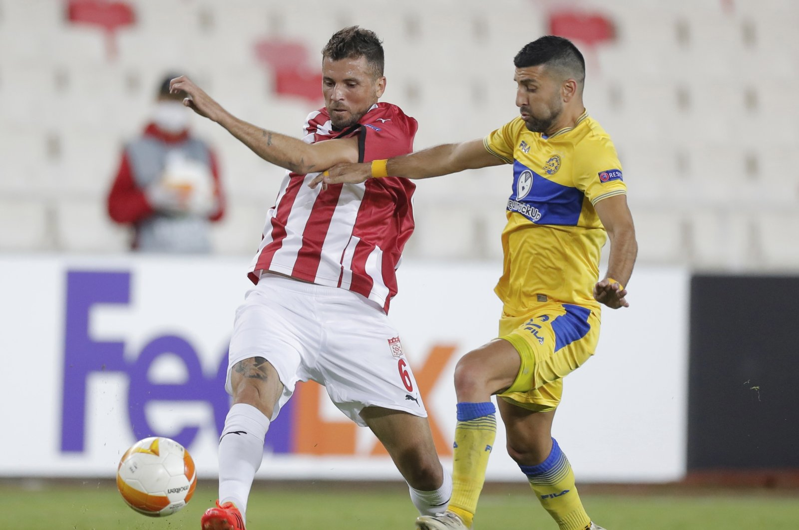 Sivasspor's Claudemir de Souza (L) and Maccabi Tel Aviv's Avi Rikan fight for the ball during the Europa League match, in Sivas, Turkey, Oct. 29, 2020. (AP Photo)