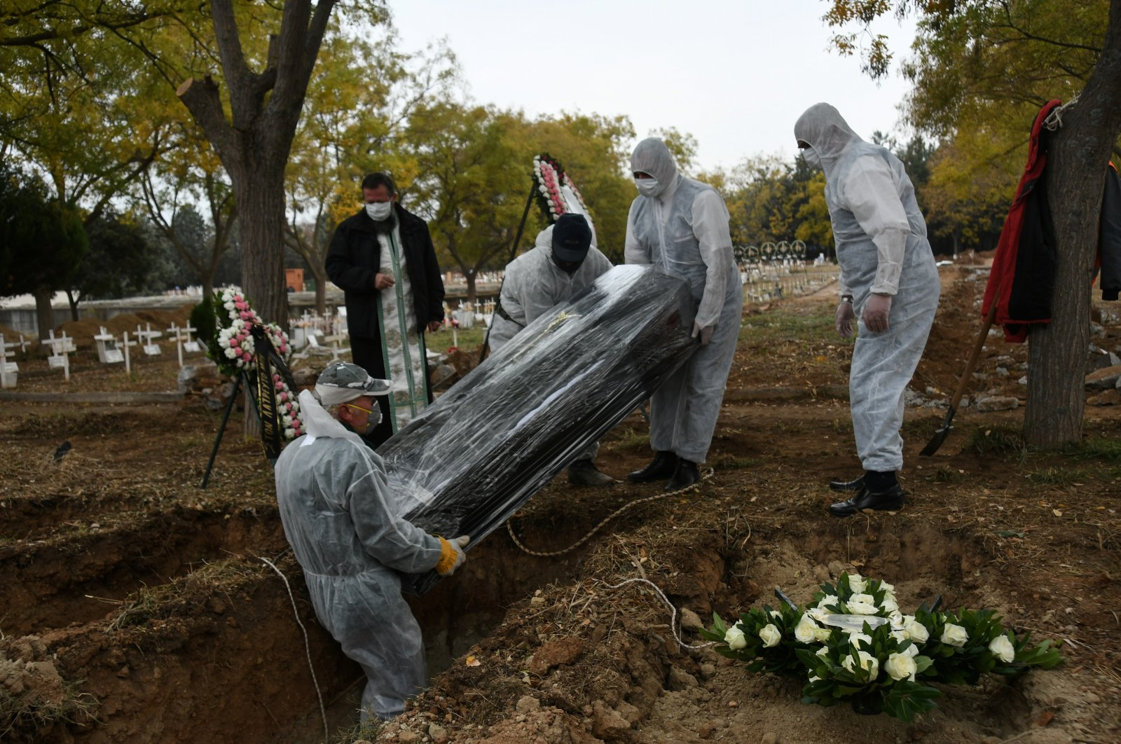 Pallbearers in personal protective equipment (PPE) place a coffin inside a grave, in a designated cemetery area for patients who died from the coronavirus disease (COVID-19), in Thessaloniki, Greece, Dec. 3, 2020. (Reuters Photo)