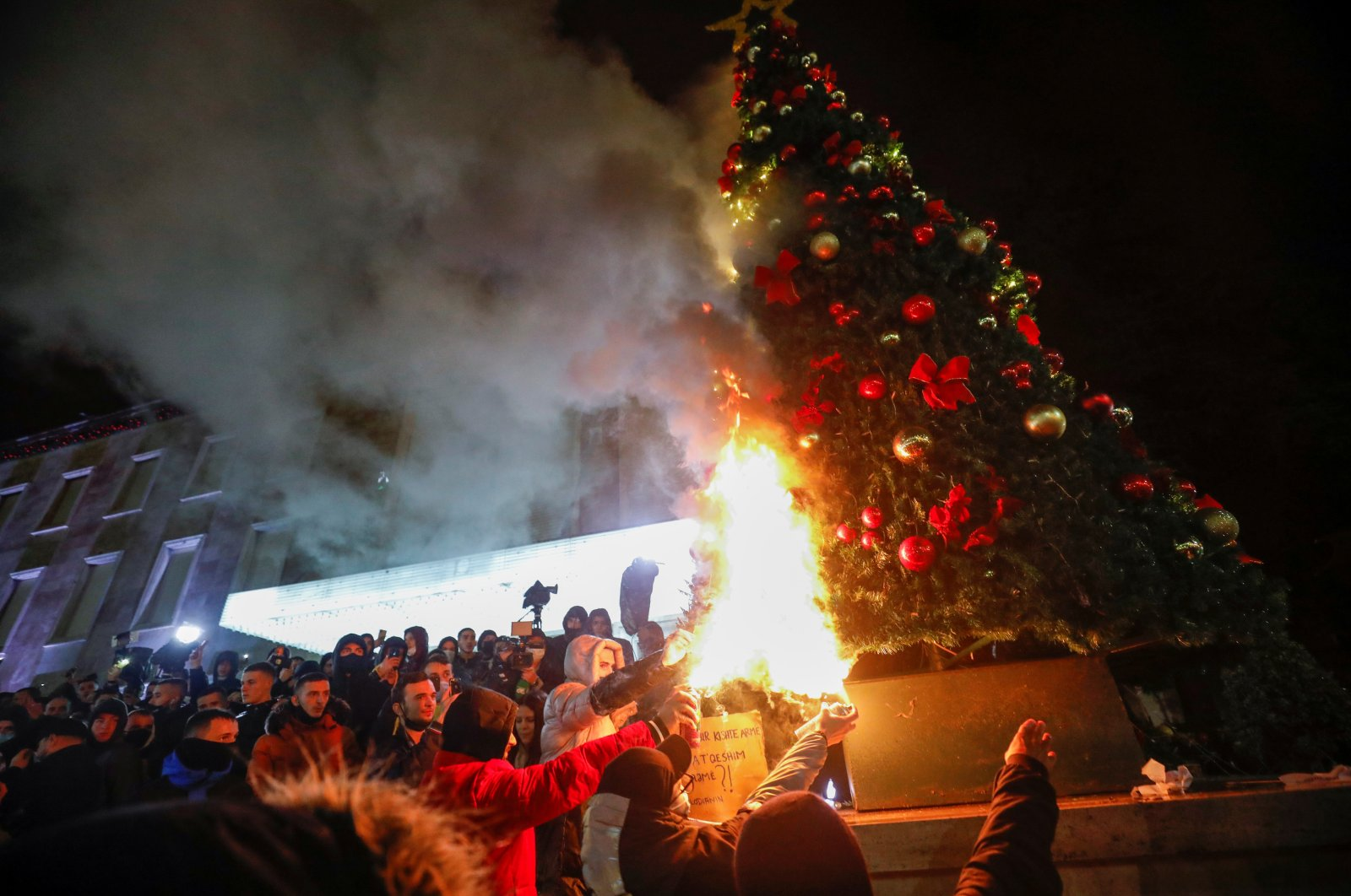 Demonstrators set fire to a Christmas tree in front of the prime minister's office during a protest in reaction to the death of Klodian Rasha, after he was shot dead during the country's overnight curfew, in Tirana, Albania, Dec. 9, 2020. (Reuters Photo)