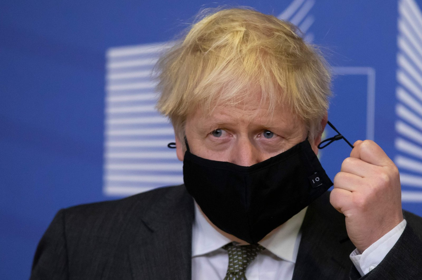 Britain's Prime Minister Boris Johnson pulls on the strings of his mask in the Berlaymont building at European Union headquarters, Brussels, Belgium, Dec. 9, 2020. (AFP Photo)