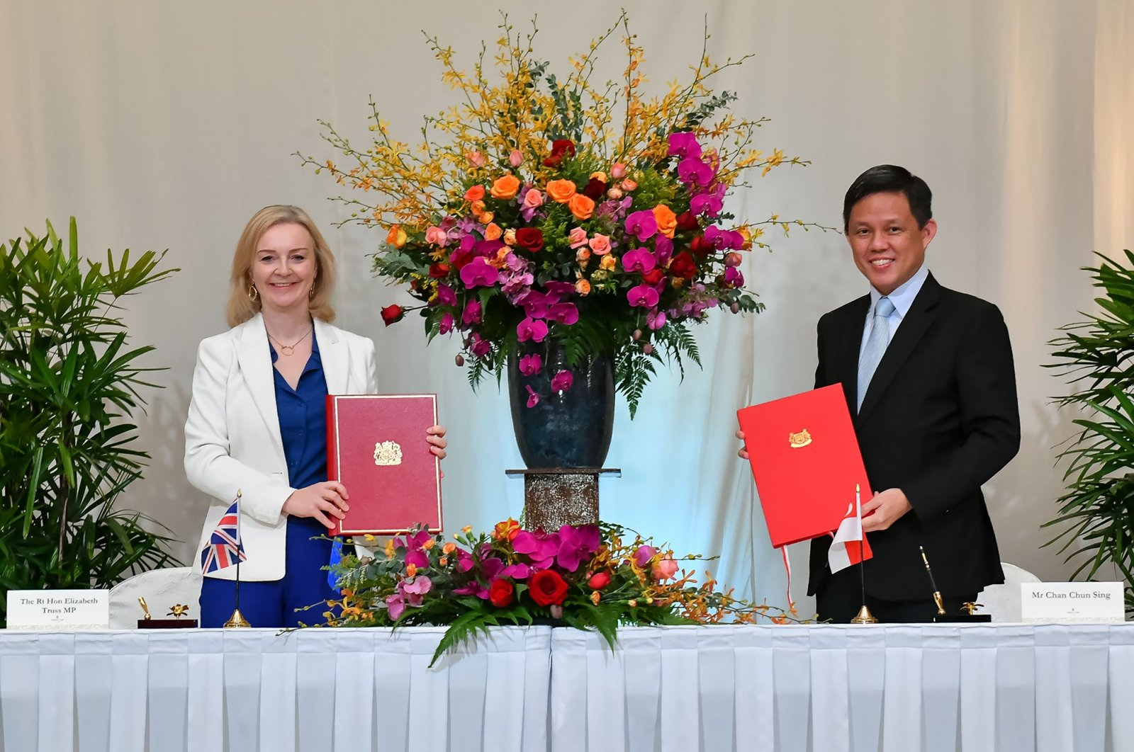 Britain's International Trade Secretary Liz Truss (L) and her Singaporean counterpart Chan Chun Sing signing a free trade deal in Singapore, Dec. 10, 2020. (Photo by Singapore's Ministry of Trade and Industry via AFP)