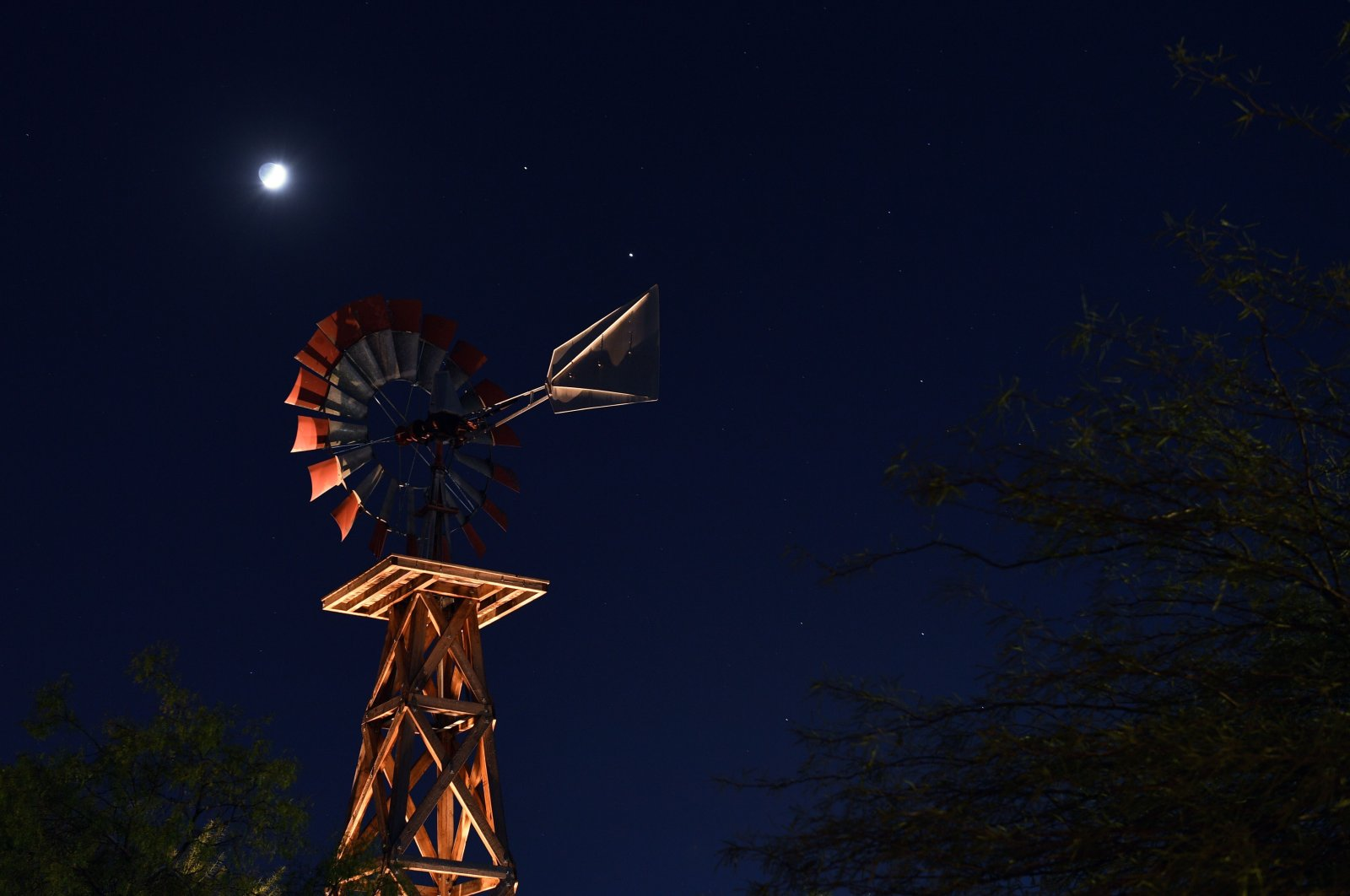 (L-R) The waxing crescent moon and the planets Saturn and Jupiter are shown above a windmill at Western Trails Park on November 19, 2020 in Las Vegas, Nevada. (AFP Photo)