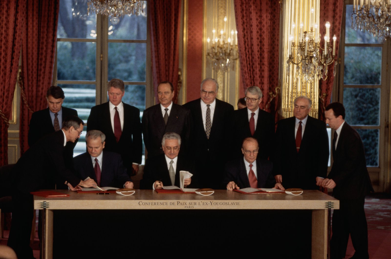 (From L to R on table) Serbian President Slobodan Milosevic, Croatian President Franjo Tudjman and Bosnian President Alija Izetbegovic sign multiple copies of the Dayton Peace Agreement as the participant other world leaders look on, in the Palais de l'Elysee, Paris, France, Dec. 14, 1995. (Photo by Getty Images)