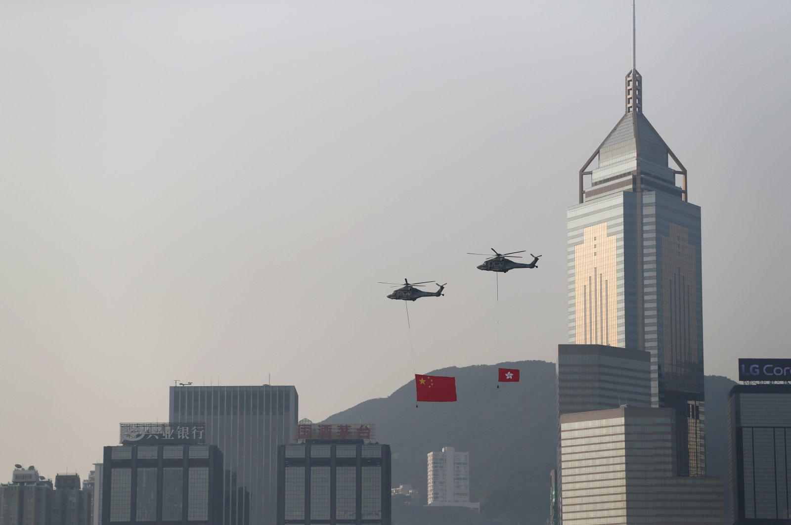 Helicopters carrying China's national flag and Hong Kong's flag fly past the skyline of Victoria Harbour on National Day in Hong Kong, China, Oct. 1, 2019. (Reuters Photo)