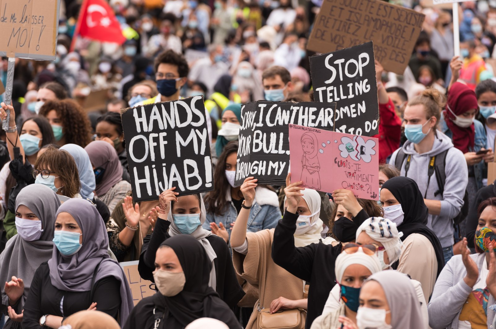 People hold placards protesting the headscarf ban at a Brussels college, Belgium, June 5, 2020. (Photo by Getty Images)