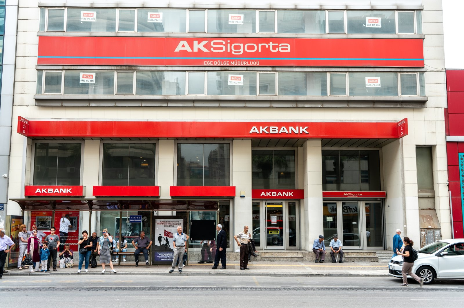 An Akbank branch is seen as people walk by and wait at a bus stop, İzmir, western Turkey, May 19, 2019. (Shutterstock Photo)