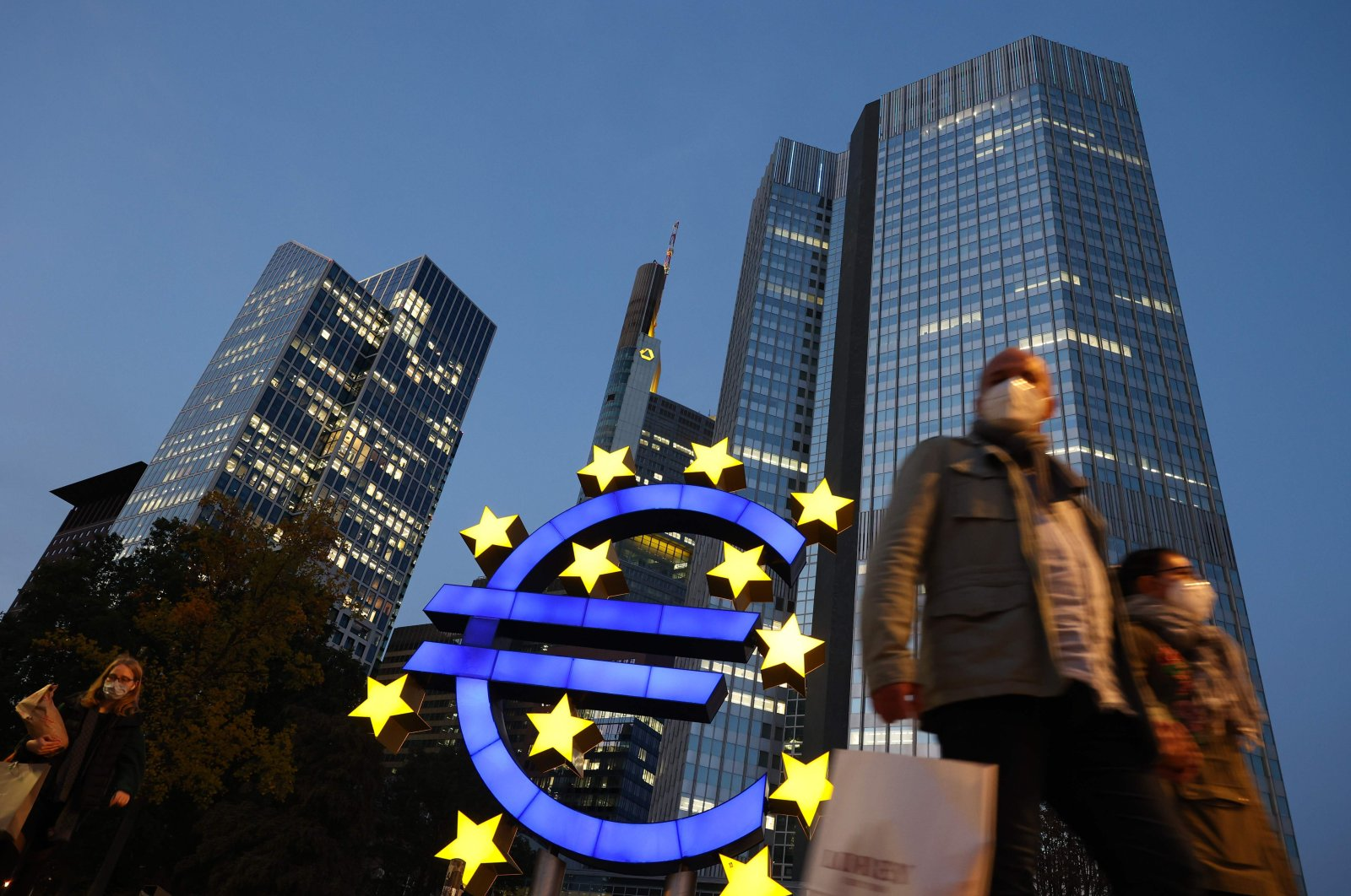 People wearing masks walk in front of the euro sign at the former European Central Bank (ECB) headquarters in the city center of Frankfurt am Main, western Germany, Oct. 21, 2020. (AFP Photo)