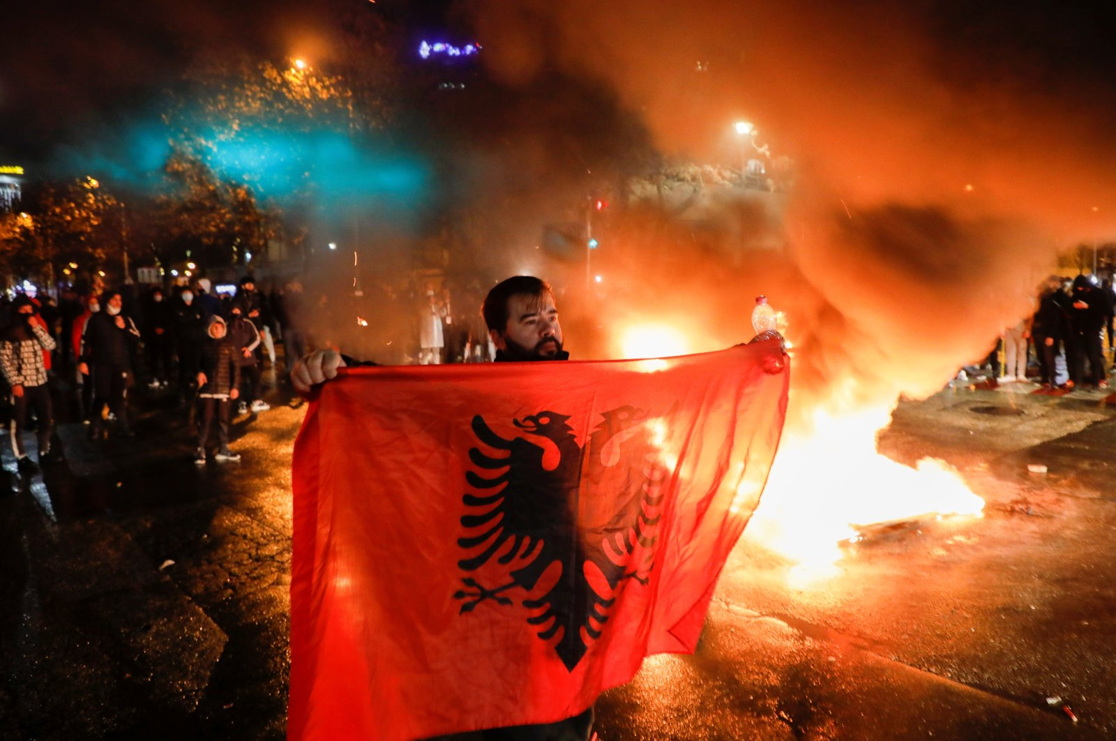 A man holds the Albanian flag as people take part in a demonstration in reaction to the death of Klodian Rasha, after he was shot dead during the country's overnight curfew, in Tirana, Albania, Dec. 10, 2020. (Reuters Photo)