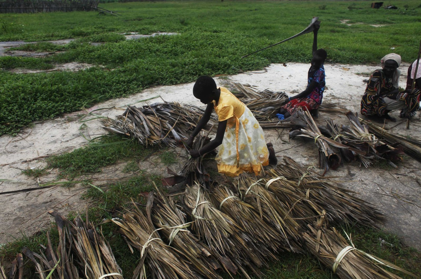 This July 17, 2014 file photo, shows girls tying dried grasses into bundles to be sold in Leer, Unity State, South Sudan. (Reuters Photo)