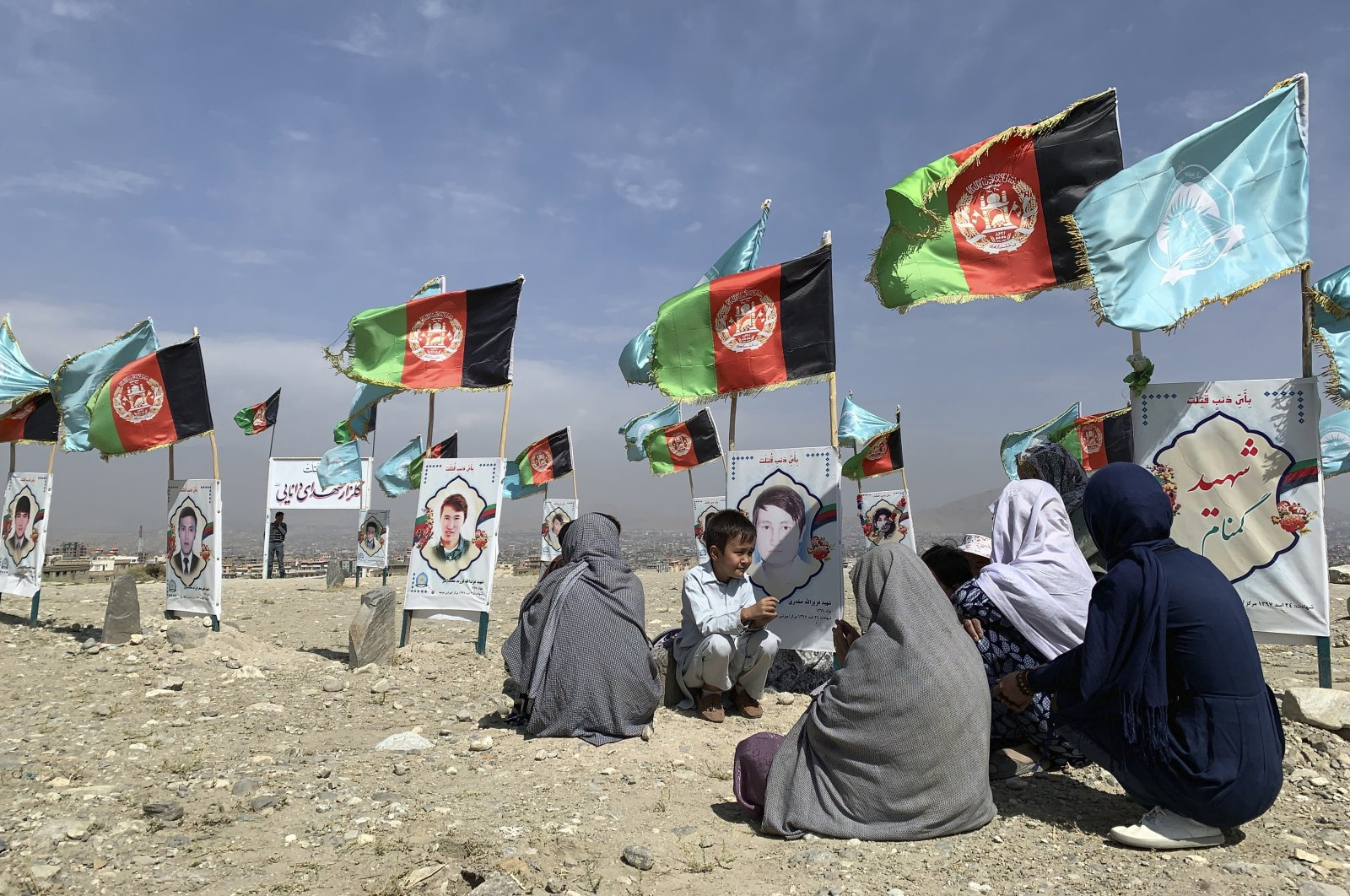 Families and friends of students who were killed in local conflicts gather at their relatives' graves, adorned with their pictures, on the outskirts of Kabul, Afghanistan, Sept. 14, 2020. (AP Photo)