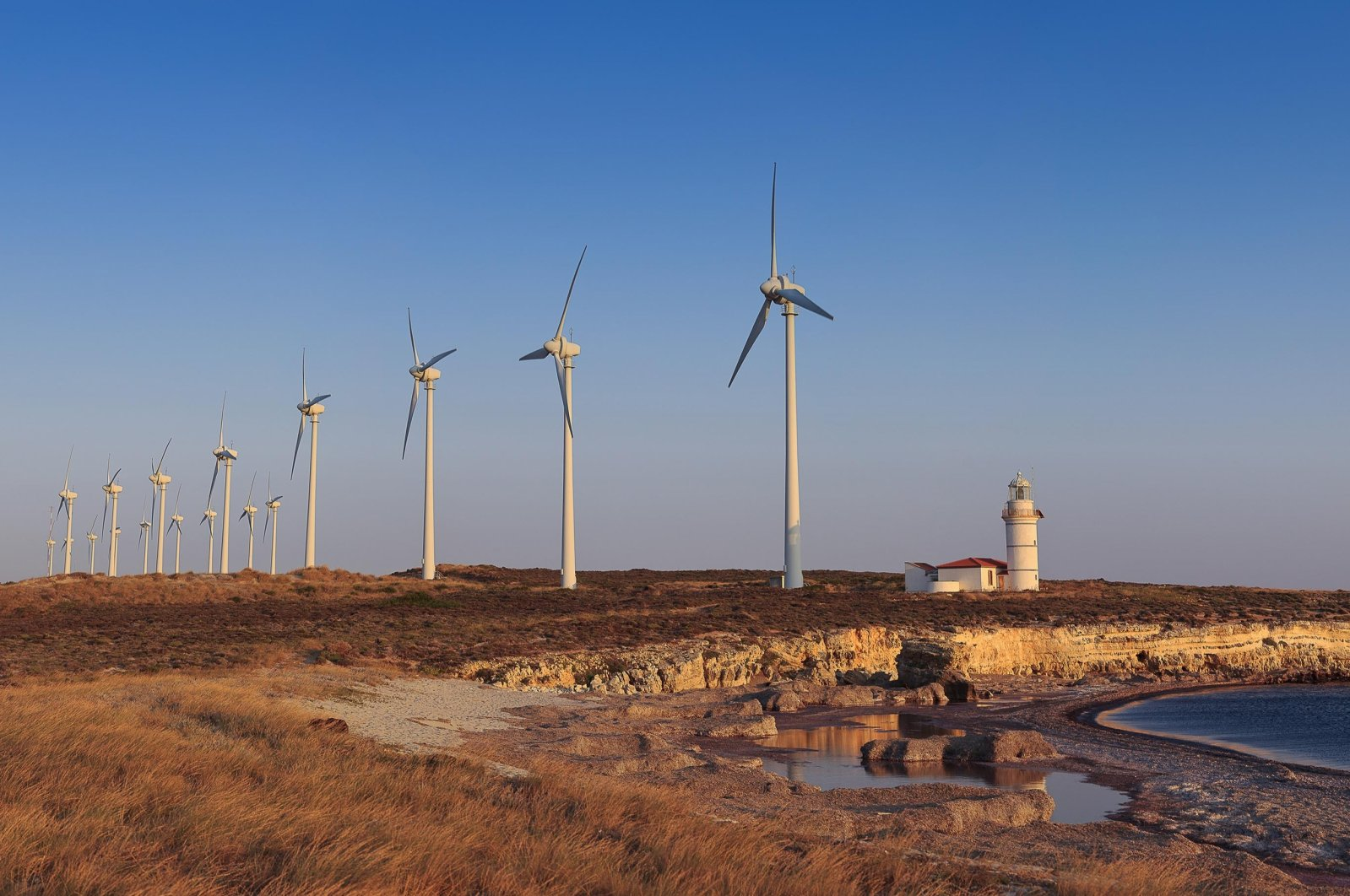 Windmills produce energy near a lighthouse on Bozcaada island near Çanakkale province, northwestern Turkey in this undated file photo. (Shutterstock photo by Serhat Akavcı)