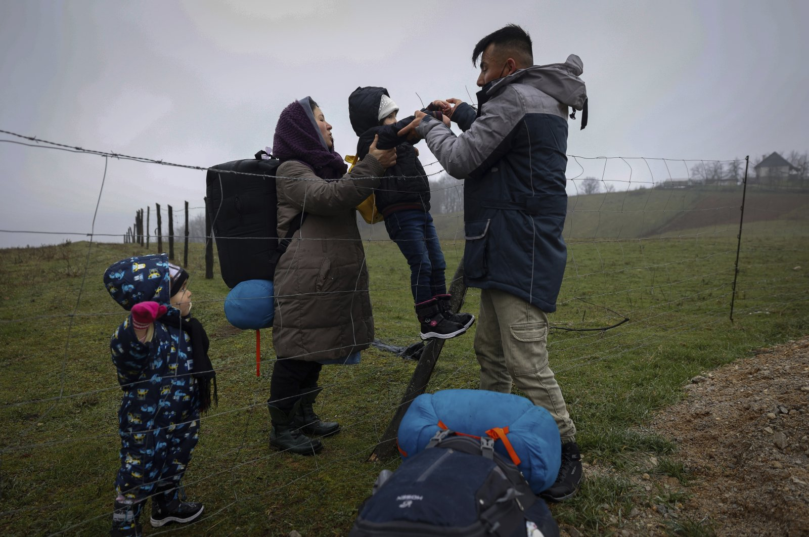 Malika, 2nd left, passes their 5 years old daughter to her husband Mohammed as the Afghan family climb over a wire fence close to the Bosnian-Croatian border near Velika Kladusa in Bosnia-Herzegovina, Dec. 9. 2020. (AP Photo)