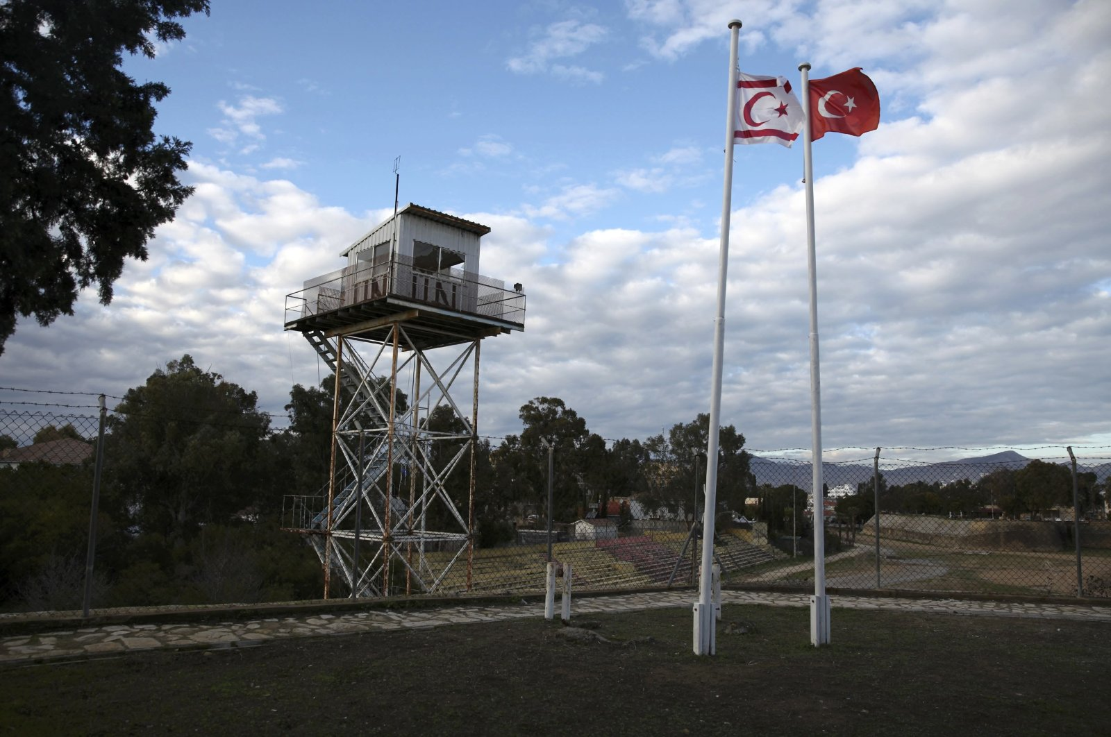 A UN guard post is seen on the buffer zone as a Turkish and a Turkish Cypriot flag wave side by side, Nicosia, Jan.12, 2017. (Reuters)