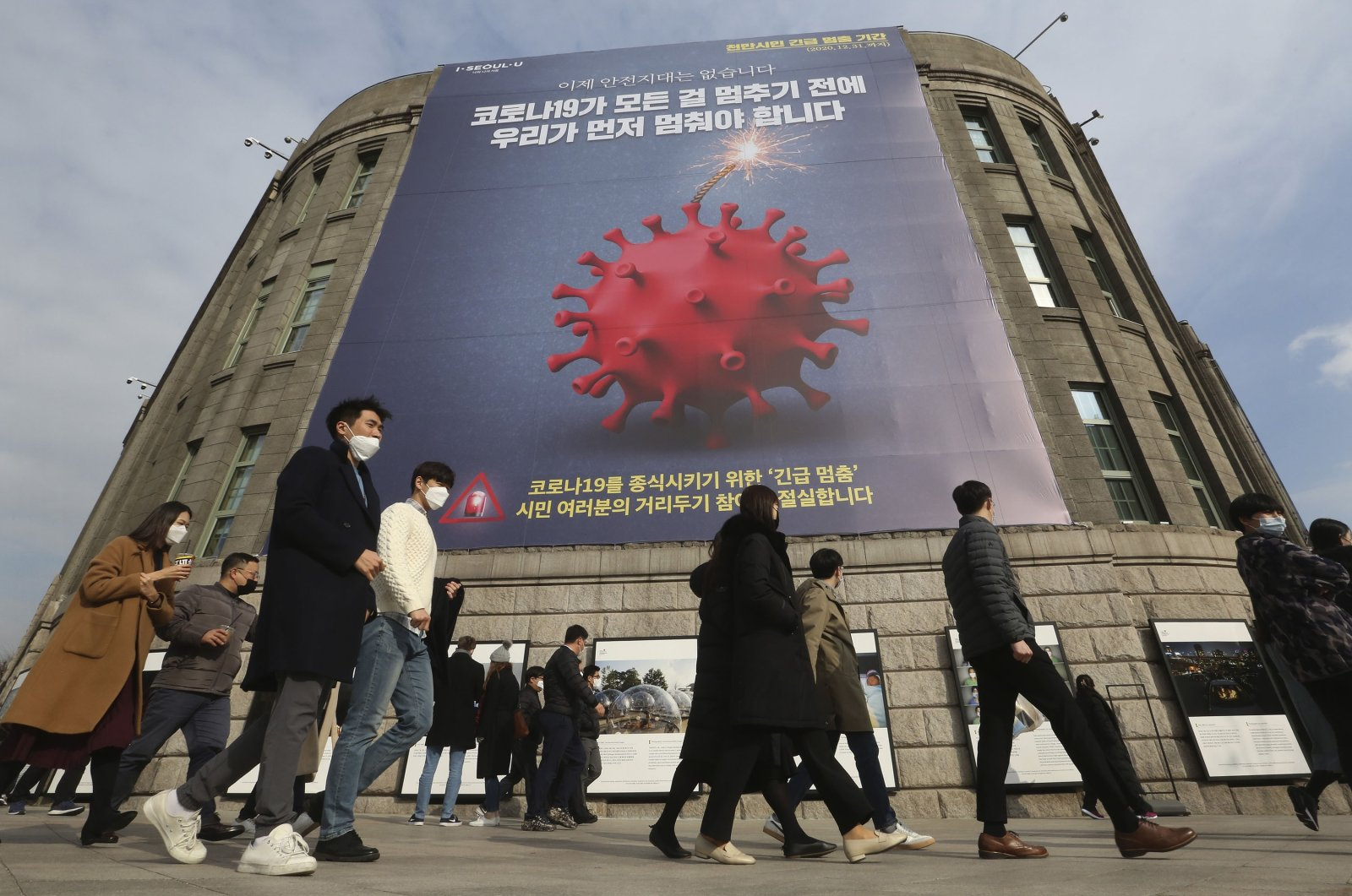 People wearing masks as a precaution against the coronavirus walk under a banner emphasizing an enhanced social distancing campaign in front of Seoul City Hall in Seoul, South Korea, on Nov. 25, 2020. (AP Photo)