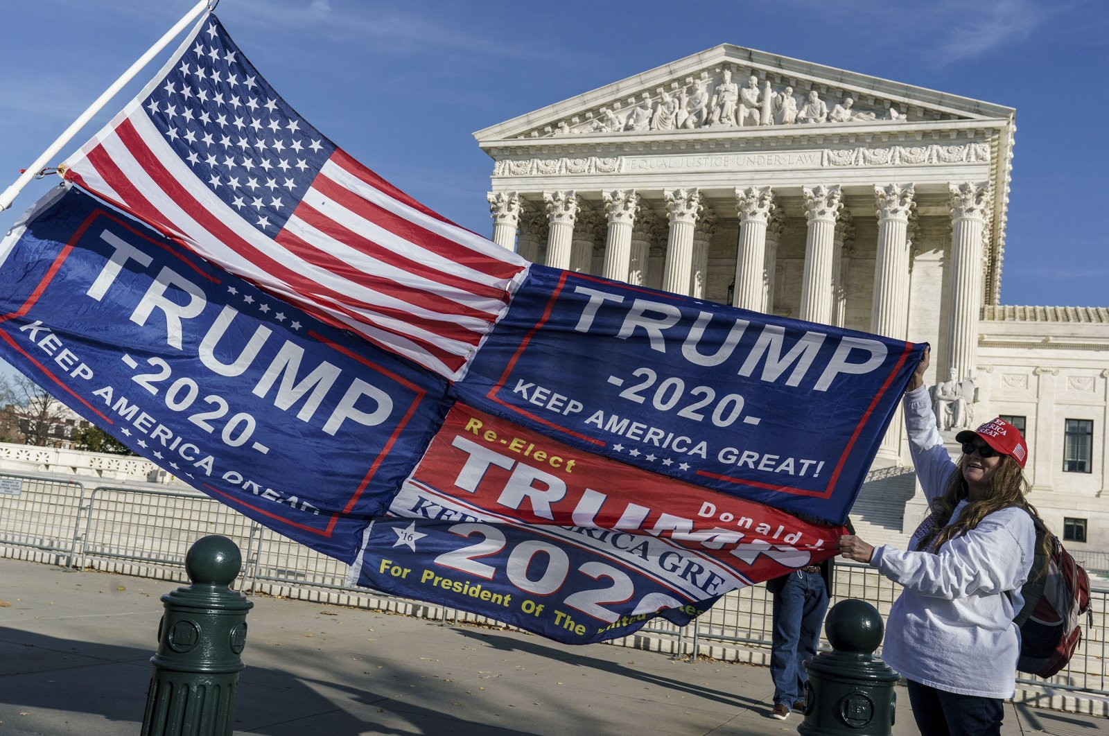 Kathy Kratt of Orlando, Florida, displays her Trump flags as she and other protesters demonstrate their support for President Donald Trump at the U.S. Supreme Court in Washington, Dec. 11, 2020. (AP Photo)