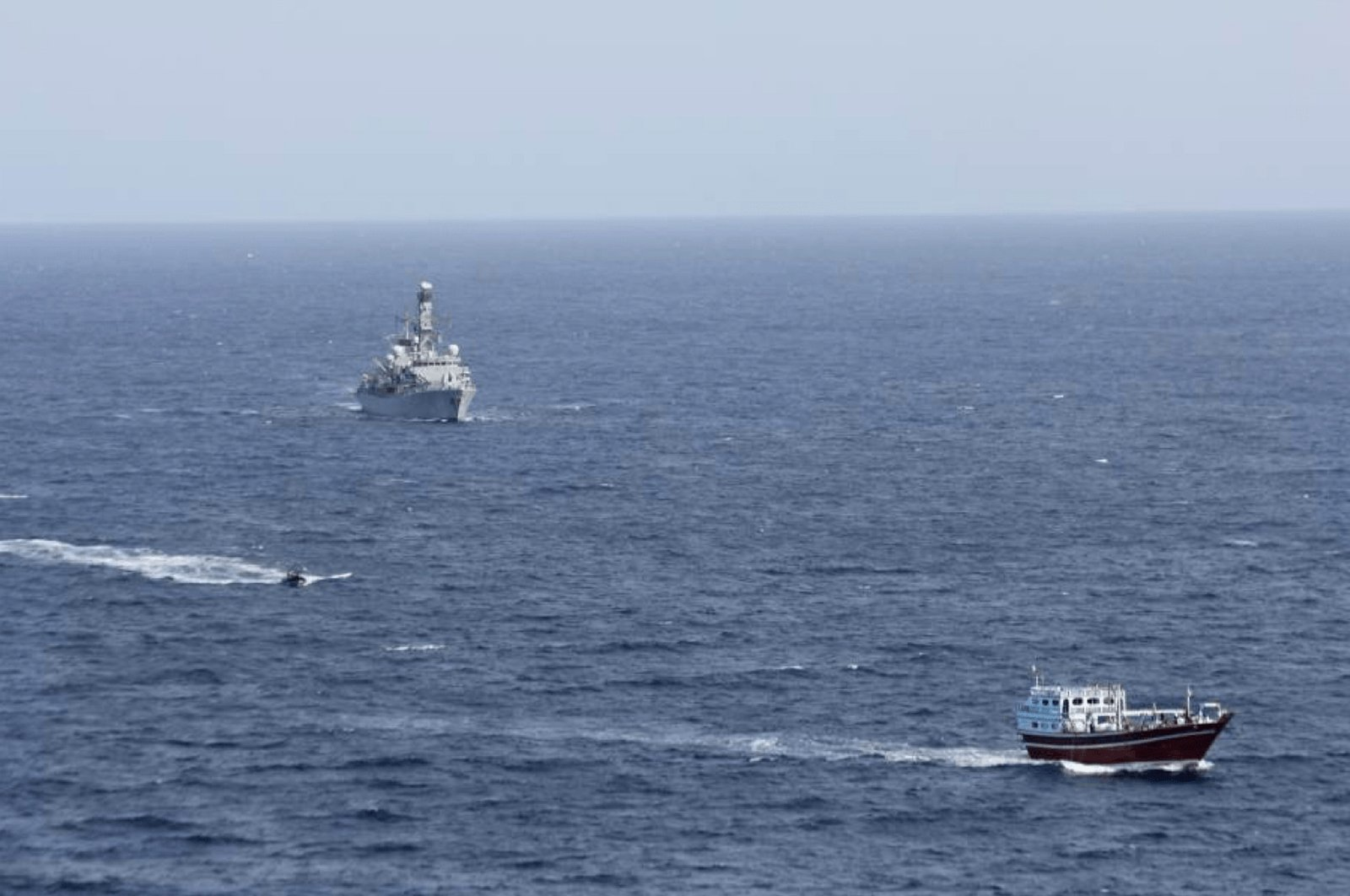 In this photo released by Combined Maritime Forces, a boarding team from a British royal navy vessel, the HMS Montrose, transits toward a stateless dhow, a traditional cargo ship that plies the Persian Gulf and surrounding waters, in the northern Arabian Sea, Oct. 14, 2020. (AP Photo)