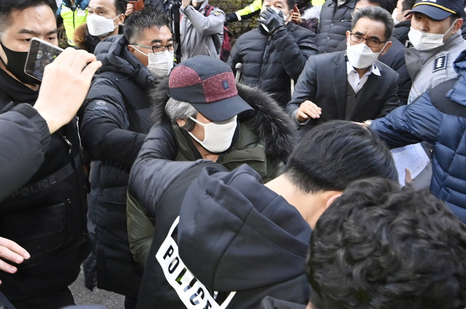 Cho Doo-soon (C), escorted by police officers, arrives home in Ansan, South Korea, Dec. 12, 2020. (AP Photo)
