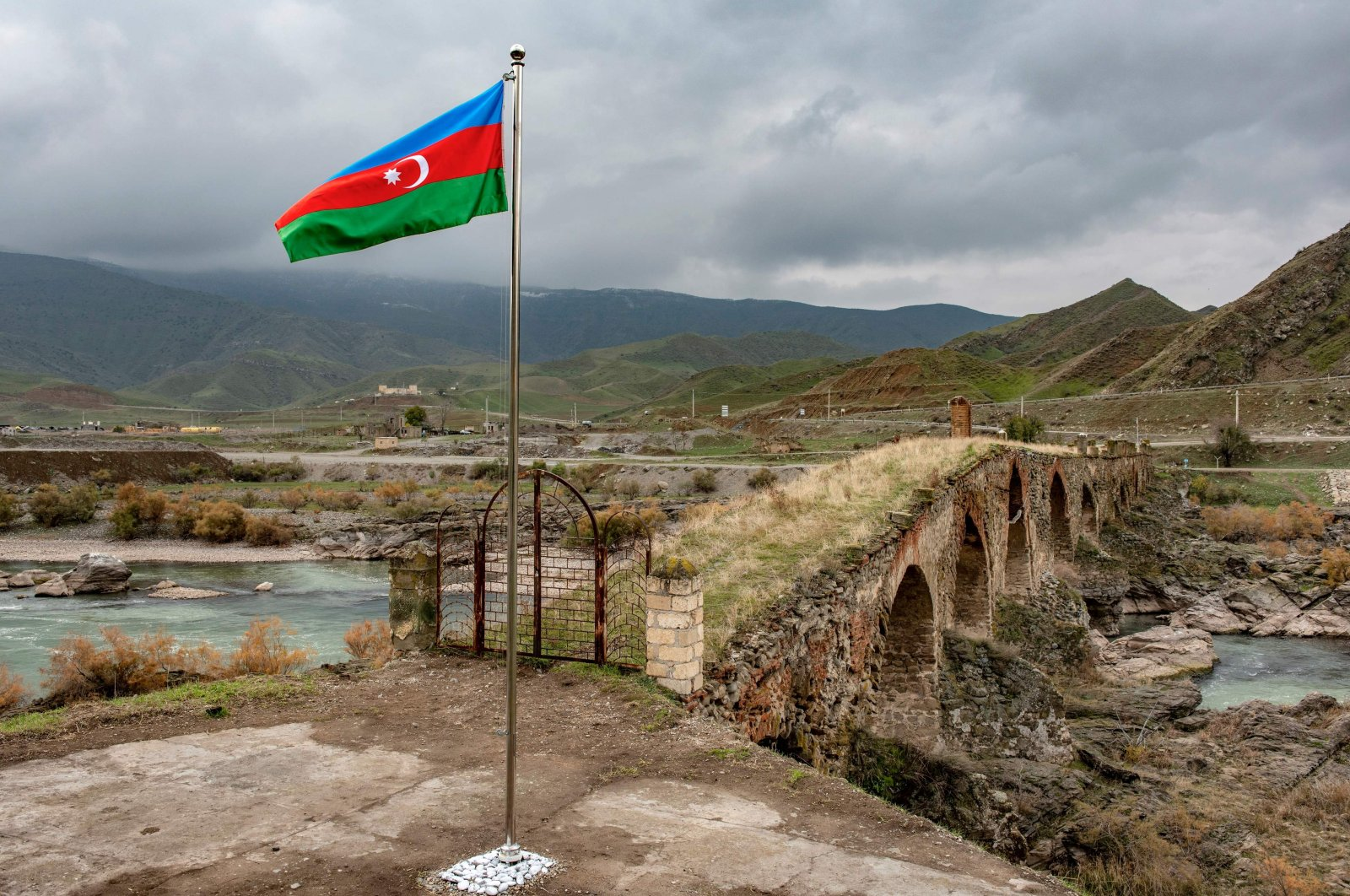 An Azerbaijani national flag flies next to the medieval Khudaferin bridge in Jebrayil district at the country's border with Iran, Azerbaijan, Dec. 9, 2020. (AFP Photo)