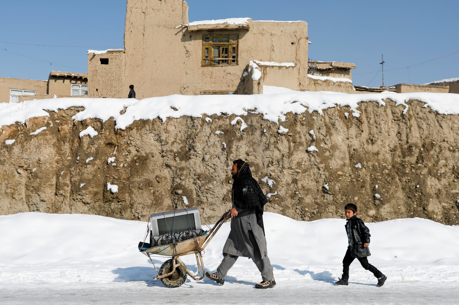 An Afghan man hauls a TV in a cart on a snow-covered street in Kabul, Afghanistan, Jan. 7, 2020. (Reuters Photo)